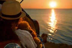 Путешественник женщины при собака сидя в багажнике автомобиля около моря, наблюдая захода солнца стоковые изображения rf