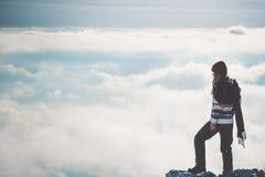 Путешественник женщины самостоятельно на скале над облаками стоковое изображение