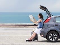 Путешественник женщины сидя на автомобиле хэтчбека на дороге взморья стоковые фотографии rf