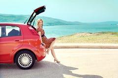 Путешественник женщины сидя на автомобиле хэтчбека с предпосылкой горы в винтажном тоне Стоковые Изображения RF