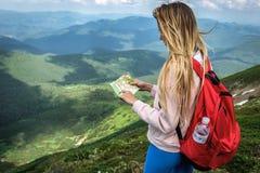 Путешественник женщины смотрит карту в Гималаях гор, острове Хонсю, Килиманджаро, Karakoram, Альп, Патагонии стоковые изображения