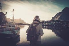 Путешественник женщины смотря заход солнца в деревне Reine, Норвегии Стоковая Фотография RF