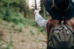 Путешественник женщины, смотря и указывая ее руку на чудесный лес стоковые фотографии rf