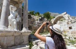 Путешественник женщины снимая старую статую с мобильным телефоном Стоковые Изображения