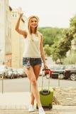 Путешественник женщины с автомобилем чемодана ждать Стоковое Фото