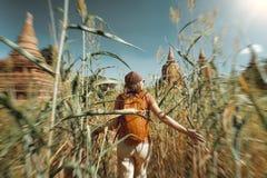 Путешественник женщины с рюкзаком бежит через поле к старому stup стоковое фото