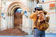 Путешественник женщины с собакой в рюкзаке делая изображения с камерой пока путешествующ стоковые фотографии rf