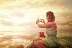 Путешественник женщины фотографируя на smartphone заход солнца, наслаждаясь c Стоковое фото RF