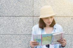 Путешественник женщин смотря карту для перемещения плана на городе стоковое изображение
