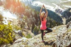 Путешественник маленькой девочки сидит na górze горы в представлении йоги Влюбленности девушки, который нужно путешествовать Конц Стоковые Изображения RF