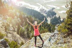 Путешественник маленькой девочки стоит na górze горы при протягиванные оружия Влюбленности девушки, который нужно путешествовать  Стоковая Фотография