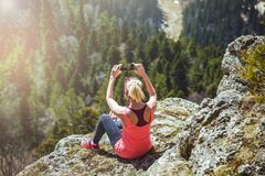 Путешественник маленькой девочки фотографирует на красивом виде smartphone от горы Влюбленности девушки, который нужно путешество Стоковое Фото