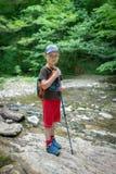 Путешественник мальчика проходит брод потока стоковые фотографии rf