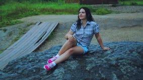 Путешественник молодой женщины сидит на огромном утесе, выполняя желания сток-видео