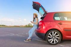 Путешественник молодой женщины сидя на автомобиле хэтчбека Стоковые Фото