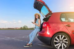 Путешественник молодой женщины сидя на автомобиле хэтчбека Стоковое Изображение RF