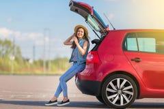 Путешественник молодой женщины сидя на автомобиле хэтчбека Стоковые Изображения RF