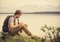 Путешественник молодого человека с книгой чтения рюкзака Стоковое Изображение RF