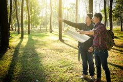 Путешественник молодого человека 2 с рюкзаком, осматривая карта ослабляя переплюнет стоковые фотографии rf