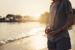 Путешественник молодой женщины с ретро камерой на пляже Стоковая Фотография RF
