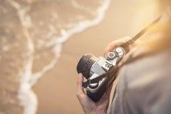 Путешественник молодой женщины с ретро камерой на пляже Стоковые Фото