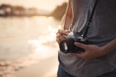 Путешественник молодой женщины с ретро камерой на пляже Стоковое Изображение
