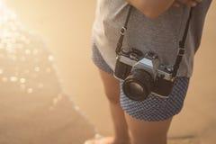 Путешественник молодой женщины с ретро камерой на пляже Стоковые Фотографии RF