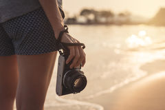 Путешественник молодой женщины с ретро камерой на пляже Стоковое фото RF