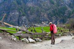 Путешественник молодой женщины фото при красный рюкзак в ландшафте лета Гималаев гор красивом на предпосылке Стоковые Изображения RF