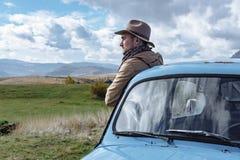 Путешественник около старого голубого автомобиля на предпосылке красивого Стоковые Фотографии RF