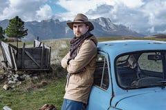 Путешественник около старого голубого автомобиля на предпосылке красивого Стоковое Изображение RF