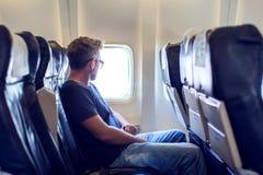 Путешественник пассажира смотря окно в самолете, перемещении flig стоковые фотографии rf