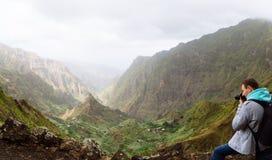 Путешественник перед ландшафтом движения Глубокие облака над зеленой долиной Xo-Xo Остров Santo Antao, Кабо-Верде стоковое фото