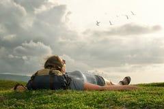 Путешественник при рюкзак смотря небо и облака над горами Стоковая Фотография