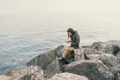 Путешественник работая на цифровой таблетке на побережье Стоковые Изображения