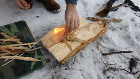 Путешественник разжигает огонь используя огниво, на месте для костра сделанного грубого камня предусматриванного при заморозок на видеоматериал
