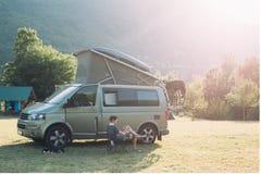 Путешественник сидит рядом с располагаясь лагерем фургоном в заходе солнца стоковая фотография