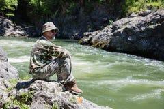 Путешественник сидит на реке. стоковые фотографии rf
