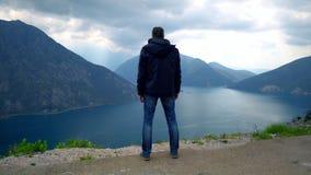 Путешественник смотря на горах в дождливом дне видеоматериал