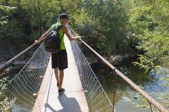 Путешественник смотря природу от висячего моста Активный и здоровый образ жизни на путешествии летних каникулов и выходных Стоковое Фото