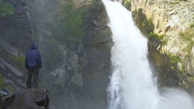Путешественник стоит рядом с водопадом видеоматериал