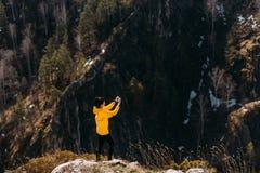 Путешественник фотографирует природу в горах на телефоне стоковая фотография