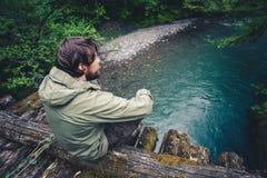 Путешественник человека ослабляя на деревянном мосте Стоковые Изображения RF