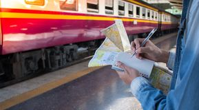 Путешественник Oung стоя около поезда самостоятельно с картой перемещения на платформе в железнодорожном вокзале Стоковая Фотография