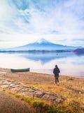 Путешественник 30s девушки Азии силуэта к стойке 40s и прогулка к озеру Стоковое Изображение
