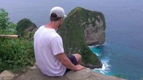Путешествовать Азии Человек на скале на заливе Manta, острове Nusa Penida, Индонезии акции видеоматериалы