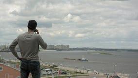 Путешествовать бизнесмена Говорить на его мобильном телефоне около реки Стоковые Изображения RF
