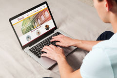 Путешествовать вебсайт в экране компьтер-книжки Человек используя его для того чтобы искать назначение перемещения стоковое фото
