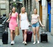Путешествовать девушки идя с чемоданами в городе Стоковые Изображения