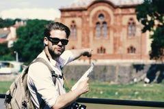 Путешествовать и концепция ориентир ориентира Человек с серьезной стороной держит карту и камеру Стоковое Изображение RF